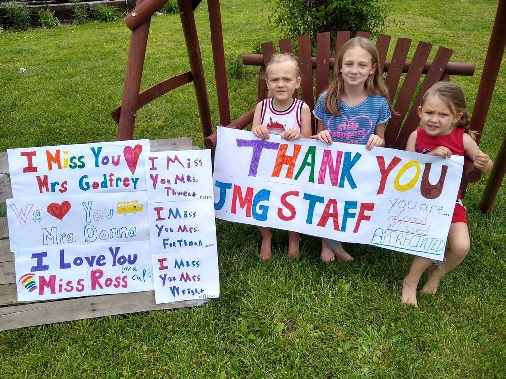 Kids on a swing holding a sign that says Thank You JMG staff